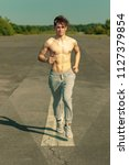 A young caucasian adult male jogging shirtless on a warm summer's day - stock photo