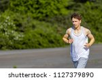 Young male caucasian adult jogging outside on a warm summer's day - stock photo