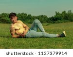 Shirtless young male dult using a mobile phone on a warm summer's day - stock photo