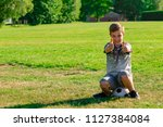 Happy pre-teen boy sitting on a football. Won a match concept - stock photo