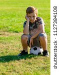 Sad looking pre-teen boy sitting on a ball. Lost game or not picked for a team concept - stock photo