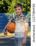 Pre-teen boy holding a basketball on a court in a park - stock photo