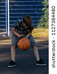 Pre-teen boy playing with a basketball in a park - stock photo