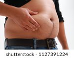 obese man in jeans squeeze the...   Shutterstock . vector #1127391224