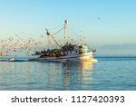 fishing boat at sea on a sunny... | Shutterstock . vector #1127420393