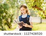 cute schoolgirl reads book... | Shutterstock . vector #1127428520