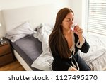 young woman sitting on bed and... | Shutterstock . vector #1127495270
