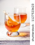 two glasses filled with whiskey ... | Shutterstock . vector #1127523623