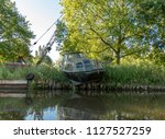 old neglected boat on the bank... | Shutterstock . vector #1127527259