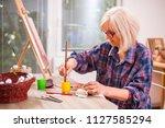 elderly woman is painting in... | Shutterstock . vector #1127585294