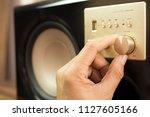 man's hand adjiusting volume... | Shutterstock . vector #1127605166