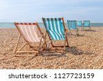 deckchairs on a shingle beach... | Shutterstock . vector #1127723159