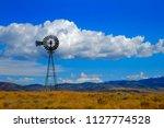 windmill on hillside in... | Shutterstock . vector #1127774528