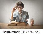 man reading a book at a desk... | Shutterstock . vector #1127780723
