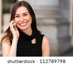 Happy businesswoman talking on her mobile phone - stock photo