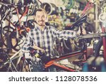 smiling man considers bicycle... | Shutterstock . vector #1128078536