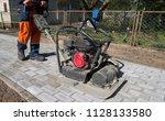 man in orange uniform using... | Shutterstock . vector #1128133580