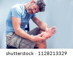 pain in the foot  man holds... | Shutterstock . vector #1128213329