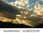 sunbeams in the clouds before... | Shutterstock . vector #1128222233