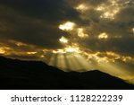 sunbeams in the clouds before... | Shutterstock . vector #1128222239