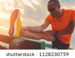 man stretching on a bench near... | Shutterstock . vector #1128230759