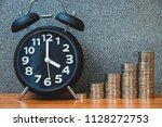 alarm clock and step of coins... | Shutterstock . vector #1128272753