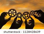 four hands of businessmen... | Shutterstock . vector #1128428639