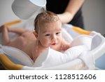mother bathing her son in white ... | Shutterstock . vector #1128512606
