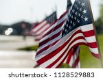 american flags in a row along... | Shutterstock . vector #1128529883
