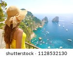 Small photo of Beautiful young female model with straw hat in Capri Island with Faraglioni sea stack and blue crystalline water on the background, Capri, Italy.