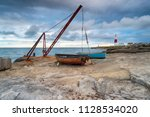 moody skies over fishing boats... | Shutterstock . vector #1128534020