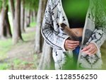young lady holding feather in... | Shutterstock . vector #1128556250