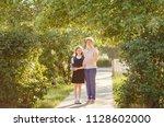 happy mom and daughter... | Shutterstock . vector #1128602000