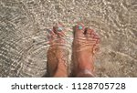 women's feet splashing in sea... | Shutterstock . vector #1128705728