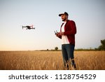 farmer holds remote controller... | Shutterstock . vector #1128754529