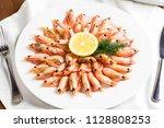 boiled shrimp with lemon on a... | Shutterstock . vector #1128808253