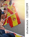 some people holding spain flags ... | Shutterstock . vector #1128912299