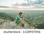 guy sitting on a rock on the... | Shutterstock . vector #1128937046
