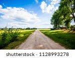 a view of a dirt road through... | Shutterstock . vector #1128993278