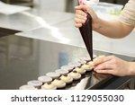 hands of confectioner cooking... | Shutterstock . vector #1129055030