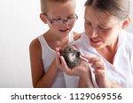 happy mother girl examines... | Shutterstock . vector #1129069556