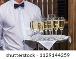 waiter holding a tray offers... | Shutterstock . vector #1129144259