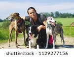 owner on a walk with her dogs.... | Shutterstock . vector #1129277156