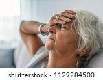 adult woman has a headache. sad ... | Shutterstock . vector #1129284500