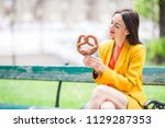 beautiful young woman eating... | Shutterstock . vector #1129287353