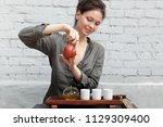 a girl in a gray linen shirt... | Shutterstock . vector #1129309400