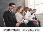 multiethnic people waiting in... | Shutterstock . vector #1129323140