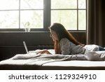 happy girl lying on bed texting ... | Shutterstock . vector #1129324910