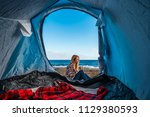 wanderlust and alternative vacation lifestyle for blonde pretty girl sitting outside of a tent camped on the sand at the beach in front of the waves of the ocean. red cover inside for the night - stock photo