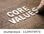 Small photo of Closeup hand arrange wood letters as CORE VALUES word